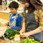 Mother and son chopping vegetables