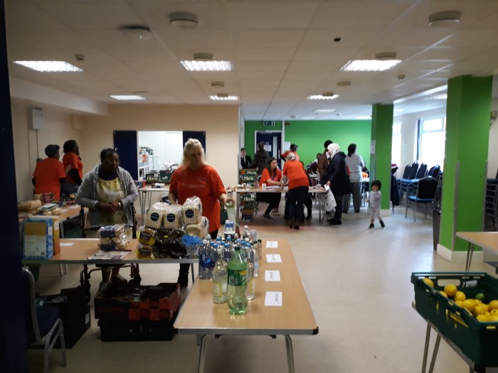 Various food products on tables and volunteers